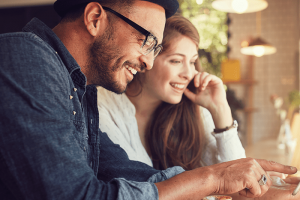 lifestyle image of a man and a woman laughing and looking at something on his phone