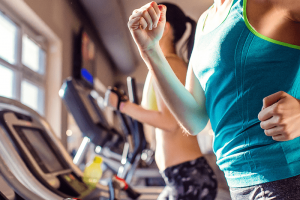 lifestyle image of a woman running on a treadmill beside others